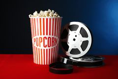 Paper cup with tasty popcorn and movie reel. On table against dark background royalty free stock image