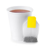 Paper cup with tea and tea bag isolated on white. Black tea in takeaway cup with tea bag  isolated on white background. Opened take-out paper cup of tea isolated Royalty Free Stock Photo