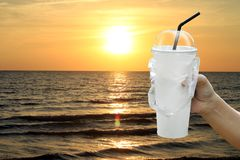 Paper cup white and straws in hand over sea beach sunset evening, fast food cup plastic for water drink is pollution waste ocean stock image