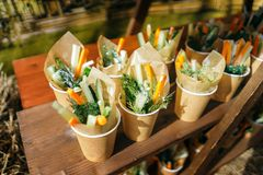 Paper cups of assorted vegetable platter - carrots, dill, orange, cucumber. Royalty Free Stock Image