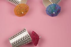Paper cups with cocktail umbrellas pink background. Top view paper cups with cocktail umbrellas pink background , summer party or summer sale concept stock photos