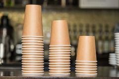 Paper cups for drinks. Paper cups stand on the bar counter stacked in three piles Royalty Free Stock Image