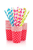 Paper cups and striped straws. Colorful paper cups and striped straws for birthday party  on white Royalty Free Stock Photos