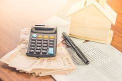 Paper currency,calculator,saving account and house model on desk. Concept of buy ,rent,pay tax for home Royalty Free Stock Photos