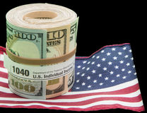Paper currency roll 1040 form US flag isolated bla. The roll of banknotes with rubber band depicts the concept of IRS income tax payment dollars using form 1040 Stock Photos