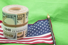 Paper currency roll 1040 form US flag rubber band. The roll of banknotes depicts the concept of USA IRS income tax payment dollars using form 1040.  The American Stock Image
