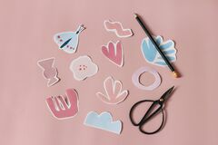 Paper cut abstract shapes, flowers and butterfly. Black old scissors and pencil on pink table background. Kids diy