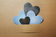 Paper cut blue and black hearts. On earthy colored paper Royalty Free Stock Photo