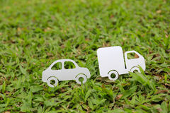 Paper cut of car and truck on green grass background Stock Image