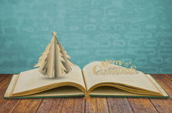 Paper cut of christmas tree on book