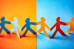 Paper cut concept - multicultural cooperation of the two groups. Orange and blue contrast colors stock photos