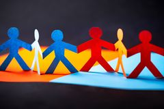 Paper cut concept - multicultural cooperation of the two groups. Orange and blue contrast colors royalty free stock photo