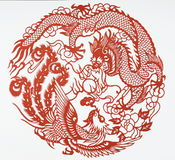 Paper cut of dragon and phoenix. Paper-cutting is a traditional Chinese folk art. The dragon and the phoenix often served in classical art and literature as Stock Photo