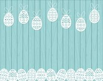 Paper cut Easter eggs hanging on blue Wooden background Royalty Free Stock Photo