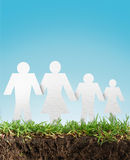 Paper cut of family on grass. White paper cut of family on fresh spring green grass Royalty Free Stock Photos