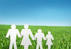 Paper cut of family on grass. White paper cut of family on fresh spring green grass Royalty Free Stock Image