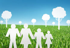 Paper cut of family on grass. White paper cut of family on fresh spring green grass with trees Stock Images