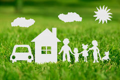 Paper cut of family with house and car. On green grass royalty free stock photos