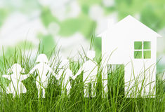 Paper cut of family with house on grass Stock Photo