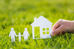 Paper cut family with house in green grass background.  Stock Photography