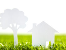 Paper cut of family house and tree on fresh spring green Stock Photo