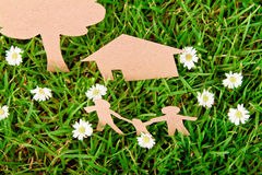 Paper cut of family with house and tree on grass. Royalty Free Stock Photography