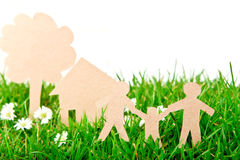 Paper cut of family with house and tree on grass. Stock Images