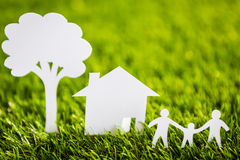 Paper cut of family with house and tree on grass Royalty Free Stock Image