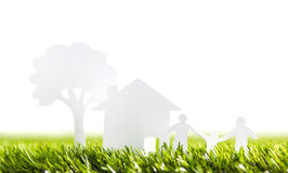 Paper cut of family with house and tree on grass. Paper cut of family with house and tree on fresh spring green grass Royalty Free Stock Images
