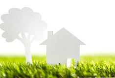 Paper cut of family with house and tree on grass Stock Image