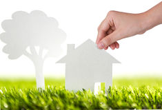 Paper cut of family house and tree on green grass Stock Images