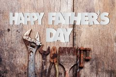 Paper cut of Happy Father`s Day text with old rusty tools on wooden background. Paper cut of Happy Father`s Day text with old rusty tools on a wooden background stock photos