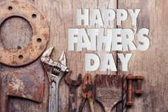 Happy Father`s Day text with old rusty tools on wooden background. Paper cut of Happy Father`s Day text with old rusty tools on wooden background royalty free stock photos