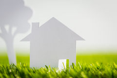 Paper cut of house and tree on green grass Royalty Free Stock Photography