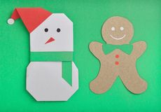 Snow man and gingerbread man. Paper cut out of Christmas snow man and gingerbread man under green background Stock Image