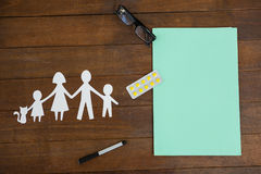 Paper cut out family chain with medicine and spectacles Royalty Free Stock Photo