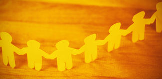 Paper cut out figures forming chain on wooden table Stock Image