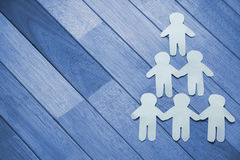 Paper cut out figures forming human pyramid Royalty Free Stock Images