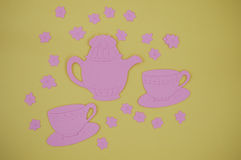 Paper cut out of pink teapot with cups and saucers Royalty Free Stock Photos