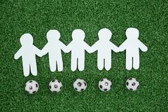 Paper cut outs and footballs arranged on artificial grass. Close-up of paper cut outs and footballs arranged on artificial grass royalty free stock photography