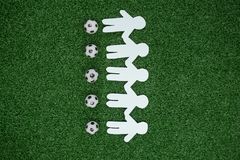 Paper cut outs and footballs arranged on artificial grass. Overhead view of paper cut outs and footballs arranged on artificial grass stock photo