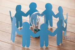 Paper cut outs forming a circle with a bulb in between Stock Photos