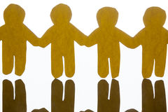 Paper cut outs holding hands together on white background Royalty Free Stock Photo