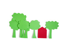 Paper cut outs of trees with a residential house over white background Stock Photos