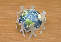 Paper cut of people standing in a circle around globe Royalty Free Stock Photography