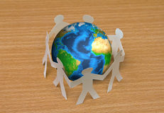Paper cut of people standing in a circle around globe Stock Photo
