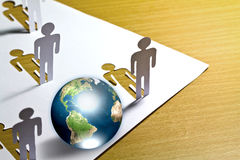 Paper cut of  people standing  with globe. Royalty Free Stock Image