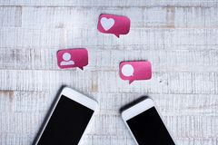 Paper Cut Social Media Icons with two Smartphones Content. On Wooden Background stock images