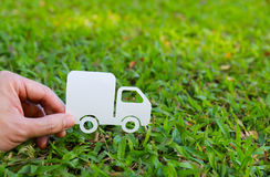Paper cut of truck on green grass background. Earth day concept, spring time Stock Photo