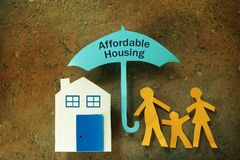 Affordable Housing family umbrella. Paper cutout family with house under an Affordable Housing umbrella royalty free stock photos